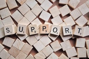 "Scrabble tiles spread across surface with some aligned to spell the word ""Support""."