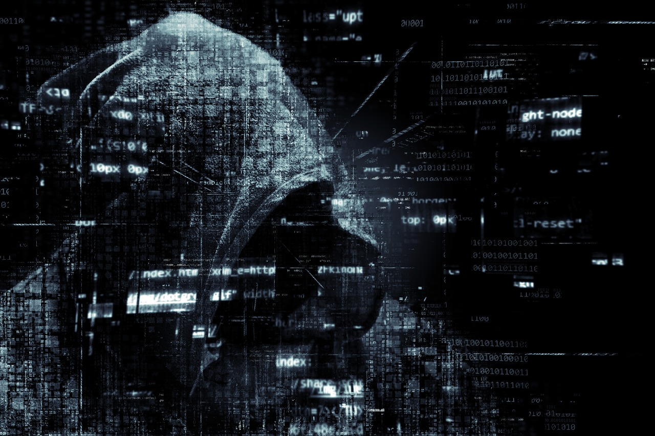 Mysterious person with hood and fragments of computer code floating around the person.