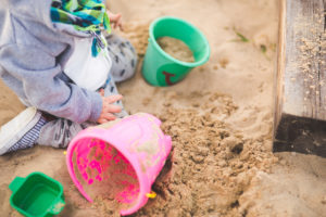 Little boy playing in a sandbox.