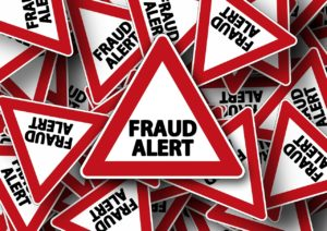 "Many signs saying ""Fraud Alert"" scattered on top of each other."
